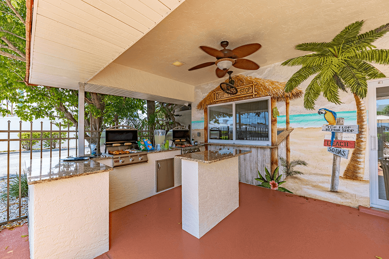Outdoor kitchen features two grills and seating area